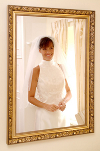 A bride on her wedding day reflected in a mirror.